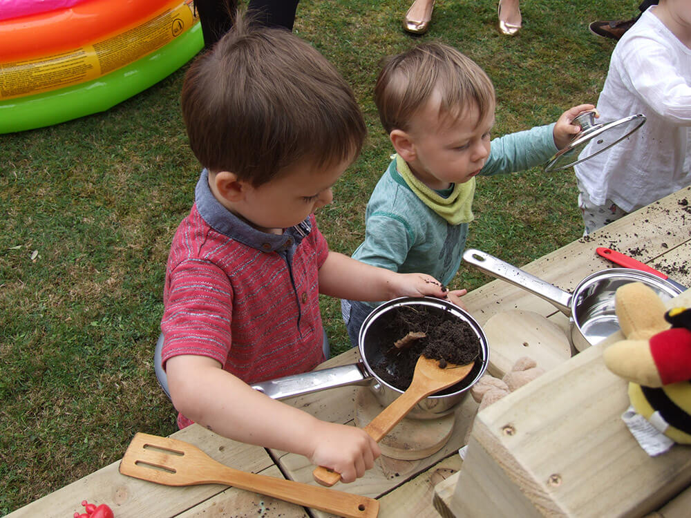 Adults & kids playing with our mud kitchen